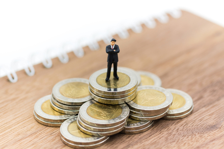 Miniature person: Businessman figure standing on stack of coins. Image use for business, financial concept. Stock Photo