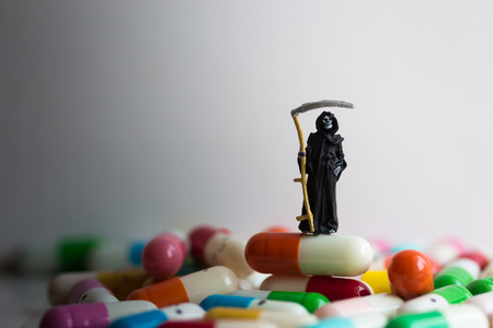 Miniature figure : The grim reaper of death stands on medicinal capsules. Image use for Misuse of drugs, Read labels before using the drug. Stock Photo
