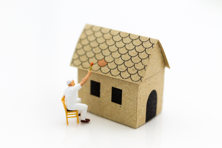 Miniature people: Workers are painting color the roof. Image use for Construction business concept.