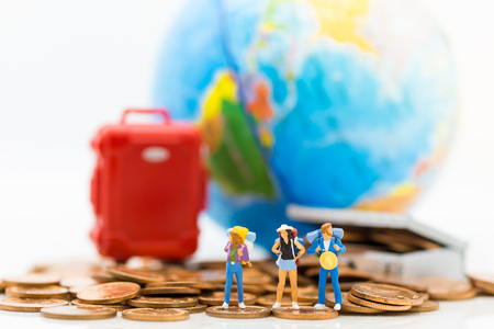 Miniature people : Travelers stand on a pile of coins and have a red suitcase, world map for background. Image use for travel, business concept. Zdjęcie Seryjne