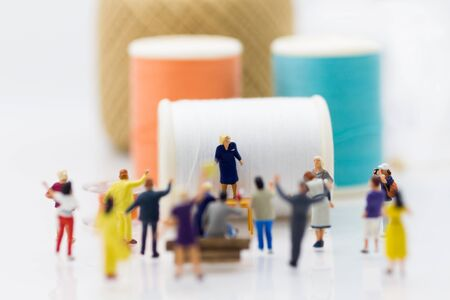 Miniature people: Group Women weaving factory protest. Image use for Claims or benefits should be earned from hard work.