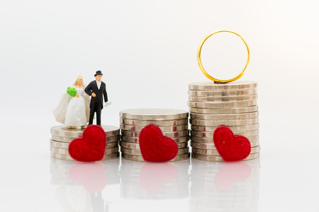 Miniature people : Bride and groom standing on stack of coins with wedding rings. Image use for saving money for marry, accumulate money for the future. Imagens