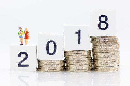 Miniature people : Brother and Sister stand on block 2018 with stack of coins. Image use for business concept. Stock Photo