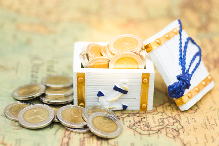 The coins in the treasure chest on the map. Image use for business concept.