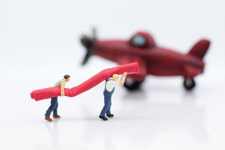 Miniature people: Workers prepare equipment for maintenance of the plane. Image use for treatment, business concept.