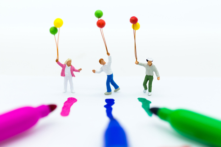 Miniature people : Children holding balloons, have color uniform  like pen color. Image use for play fun in childhood, childrens day Stock Photo