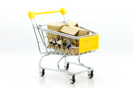 Miniature people: Group businessman sitting on shopping cart for retail business. Image use for online and offline shopping, marketing place world wide. Stock Photo