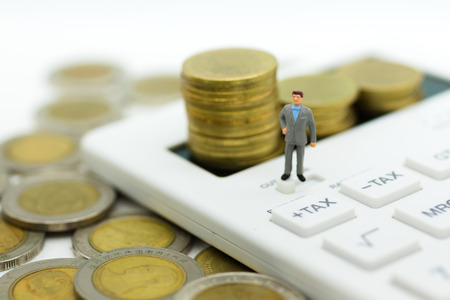 ミニチュアの人々:ビジネスマンは、電卓、計算税毎月毎年立っています。すべての人のための毎年の税の計算のための画像の使用。