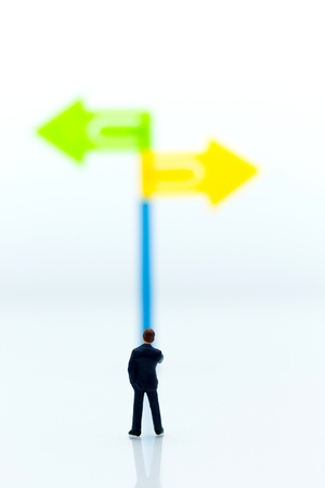 Miniature people: Businessman standing in front of arrow pathway choice. Image use for business decision concept, new the way.