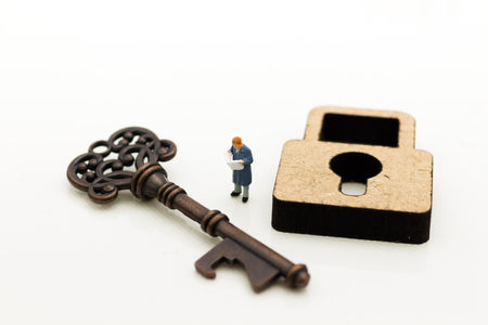 Miniature people: Businessmen stand with master key and reading newspaper. Image use for key man, the key to success, business concept. Stock Photo