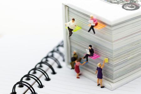 Miniaturleute: Geschäftsmannlesezeitung auf einem großen Buch. Bildgebrauch für Hintergrundbildung oder Geschäftskonzept.