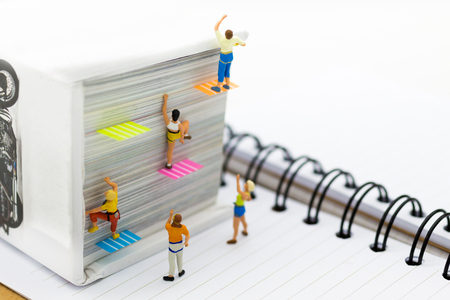 Miniature people: Climber climbing on book . Image use for learning, education concept. Фото со стока