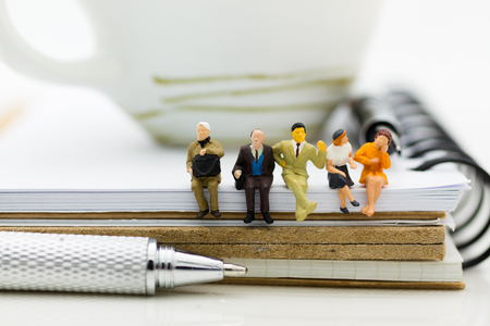 Miniature people : Business team sitting on book and having a coffee break. Image use for business concept.