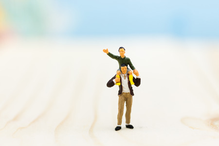 Miniature family: Father gave the son a ride on the neck. Image use for expressed love between the family, the lineage.