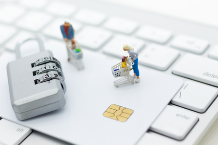 Miniature person: a shopper pushes a shopping cart with credit card. Image use for security of using internet to shopping online, Concept retail business increased competition from internet online e-commerce. Stock Photo
