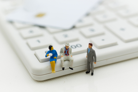 Miniature people: Businessman sitting on calculator for calculating money, tax, monthlyyearly. Image use for finance, business concept.