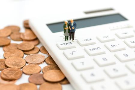 ミニチュアの人々:電卓の上に立っているカップル。すべての人のための毎年の税の計算のための画像の使用。