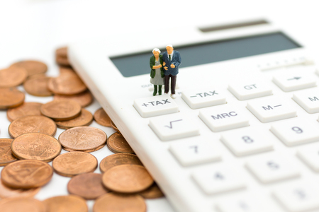 Miniature people: Couple standing on the calculator. Image use for Tax calculation every year for everyone. 写真素材