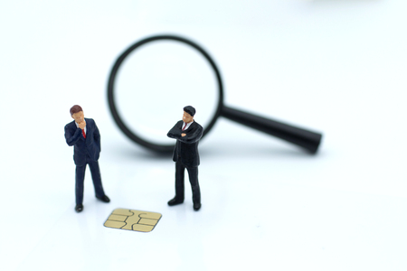 Miniature people: Businessman with a credit card chip. Image use for business concept