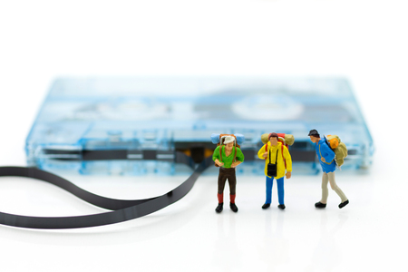 Miniature people: backpacker walking on Compact Cassette. Image use for music of travel, business concept.