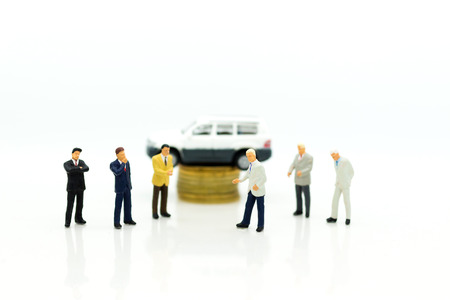 Miniature people : Businessman standing with car. Image use for Advertising product in the market today, competition on the business trading. 写真素材