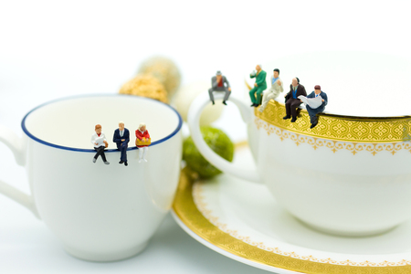 Miniature people : Business team sitting on cup of coffee and having a coffee break. Image use for business concept. Stock Photo