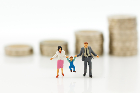 Miniature people, family figure standing on top of stack coins . Image use for background retirement planning, Life insurance concept.