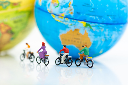 Miniature people : People group riding bicycle with world map. Image use for sport, travel and business concept. Banque d'images