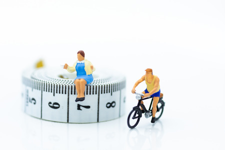 Miniature people : woman sitting on tape Measure and eat snack ,and man riding bicycle for healthy. Image use forHealth care and diet concept.