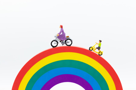 Miniature people : Mom and kids cycling on the rainbow. Image use for to be good model, family concept.
