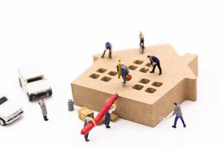 Miniature people: Workers are helping to build a house. Image use for teamwork, business concept.