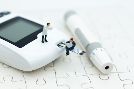 Miniature people sitting on glucose meter with lancet. Image use for medicine, diabetes, health care concept.