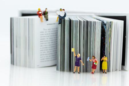 Gente en miniatura: los estudiantes leen libros, mantienen libros en estanterías. Uso de imágenes para el concepto de educación.