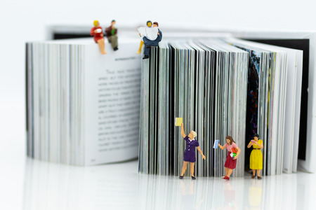 Miniature people: Students read books, keep books on bookshelves . Image use for education concept.