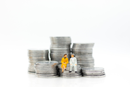 Miniature people, adult couple figure standing on top of stack coins . Image use for background retirement planning, Life insurance concept. Standard-Bild