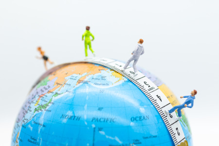Miniature people running on waistline with world map . Image use for healthy , exercise concept.
