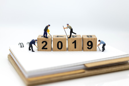 Miniature people : Worker using tools with wooden block 2019 .Image use for new year, business concept.