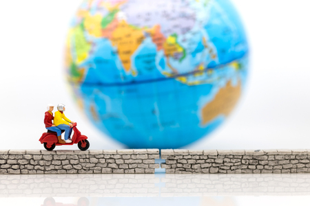 Miniature people : Tourist Drive a motorcycle along the wall, world map for background. Image use for security of data, network system concept.