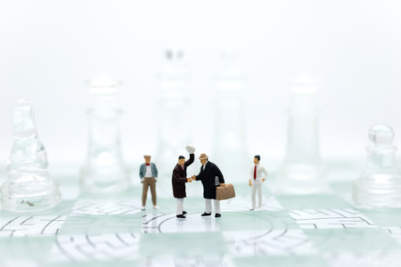 Miniature people, Group Businessmen standing on the chess game with graph background, thinking solution for the business game,  use as a business competition concept.