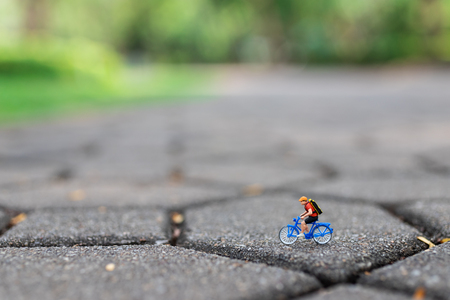 Miniature people : Travelers riding bicycle on the road. Image use for background traveling  business concepts.