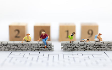 Miniature people : Businessman sitting on the wall and have wooden block 2019. Image use for business , happy new year concept. Stock Photo