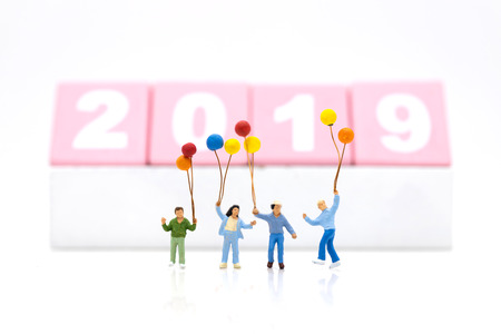 Miniature family, children holding colorful balloon. Image use for background International day of families, happy new year 2019 concept. Stock Photo