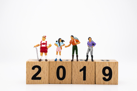 Miniature people: People standing on top of wooden block 2019, happy new year . Image use for business, travel concept.