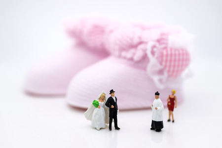 Miniature people : Bride and groom wear wedding suit and waiting for baby in the future . Image use for make new family.