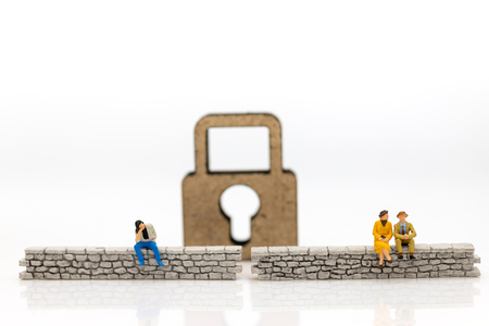 Miniature people: Businessman sitting on the wall and have master key is inside. Image use for business security center, protect concept
