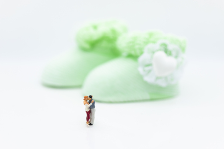 Miniature people : Man and woman hug together, waiting for baby in the future . Image use for make new family.