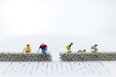 Miniature people : Businessman sitting on the wall . Image use for business , spend time for family.