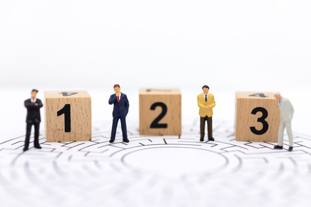 Miniature people : Businessman standing on wooden blocks with sequential numbers. Image use for business concept.
