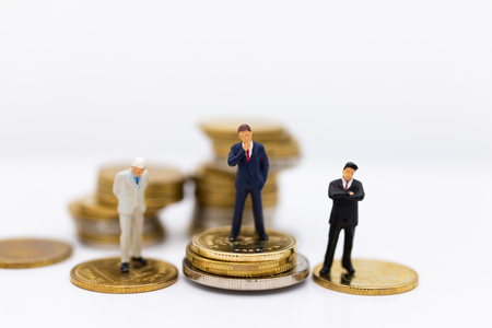 Miniature businessman and stack of coins. Image use for investment, saving money.
