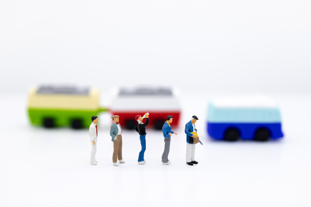miniature people, backpack waiting bus at bus station for travel. using as business background concept.